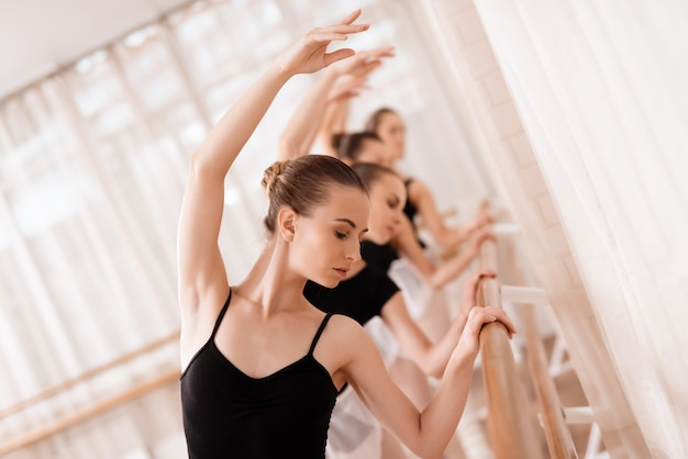 Ils forment des mouvements de danse. ils utilisent une barre de ballet.