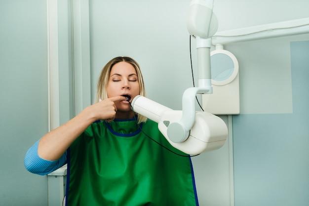 Ils prennent une photo de la jeune fille dans le cabinet dentaire de radiologie de l'hôpital.
