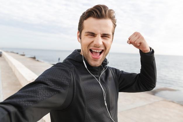 Image de 30 s sportif excité en vêtements de sport noirs et écouteurs, prenant une photo de selfie sur un téléphone mobile tout en marchant au bord de la mer