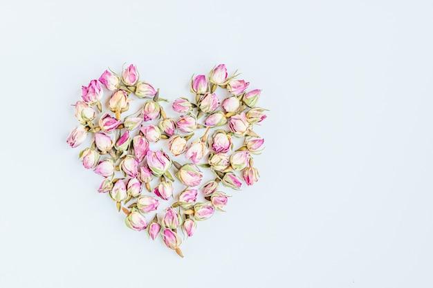 Image abstraite d'un coeur composé de boutons de roses séchées.