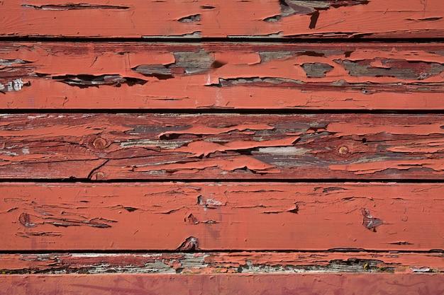 Image abstraite de décoloration de la peinture rouge sur un ancien bâtiment en bois extérieur