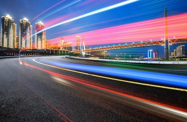 Image abstraite du mouvement flou de voitures sur la route de la ville la nuit, architecture urbaine moderne à chongqing, chine