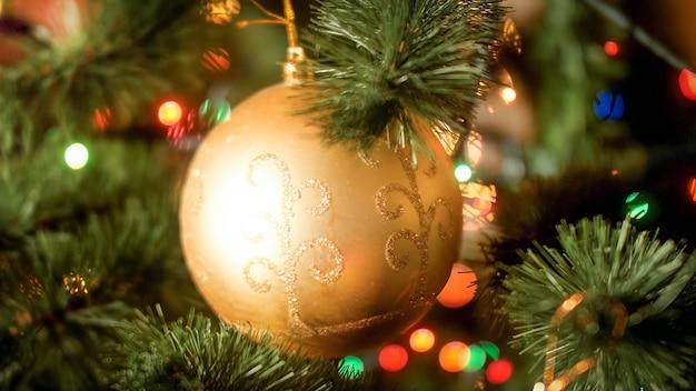 Image abstraite gros plan de la boule dorée avec des étincelles accrochées à une branche d'arbre de noël. arrière-plan parfait pour les vacances d'hiver et les célébrations