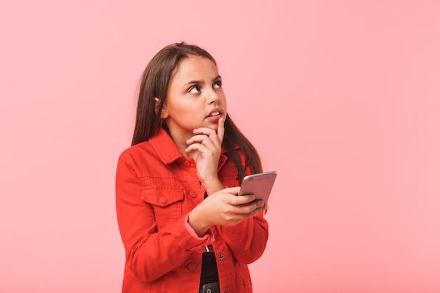 Image d'une adolescente perplexe dans l'utilisation occasionnelle de téléphone portable en position debout, isolé sur mur rouge