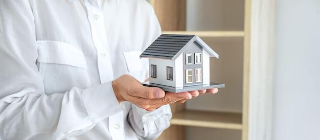 Image de l'agent de courtage immobilier envoyant le modèle de maison au client après approbation