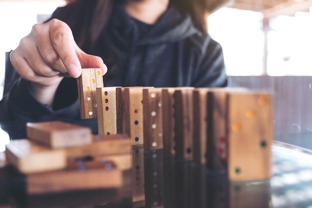 Image agrandi d'une femme mettant jeu de domino en bois dans l'ordre sur la table