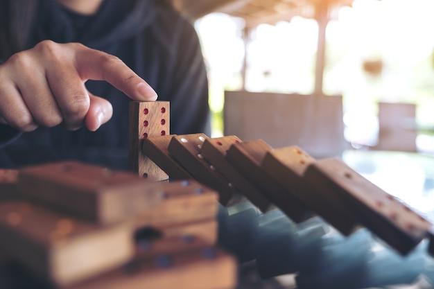 Image agrandi d'une main essayant d'arrêter le jeu de domino en bois de tomber sur la table