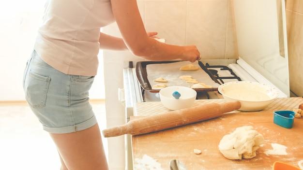 Image agrandi tonique de la jeune femme mettant la pâte sur la plaque de cuisson. femme faisant et faisant des biscuits sucrés à la maison