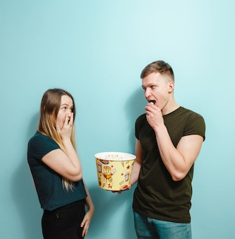 Image d'amis heureux isolés tenant un film de montre pop corn.