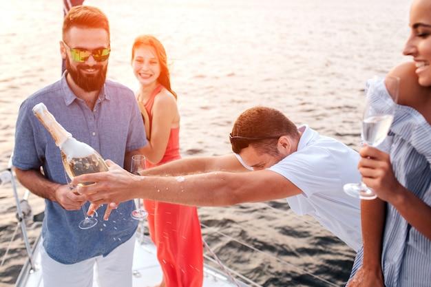 Image amusante d'un homme tenant une bouteille de chmpaigne devant lui. tout le monde tient des lunettes. ils sourient. le gars devant porte des lunettes de soleil