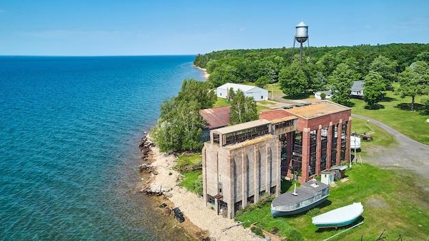Image de l'antenne de l'ancien bâtiment abandonné en brique et en ciment et du château d'eau sur la côte du lac
