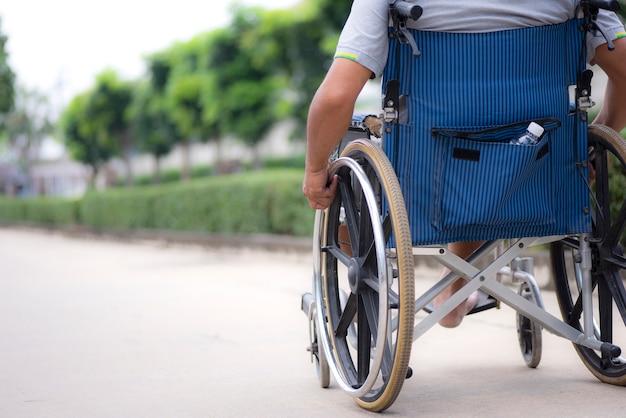Image arrière du fauteuil roulant âgé lors d'une promenade dans le parc