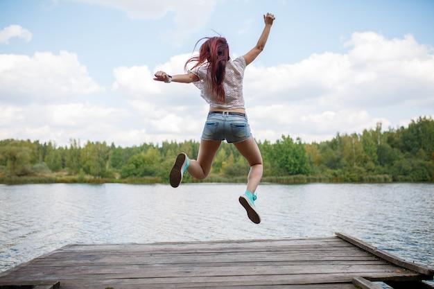 Image de l'arrière d'une jeune femme sautant sur un pont en bois au bord de la rivière