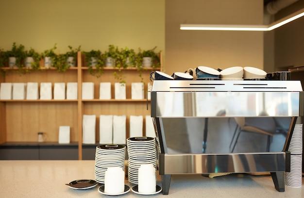 Image d'arrière-plan aux tons chauds du café en mettant l'accent sur la machine à café et les tasses, espace de copie