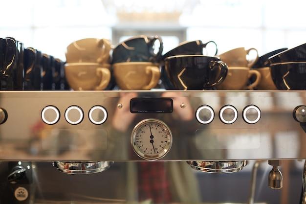 Image d'arrière-plan aux tons chauds d'une machine à café en acier dans un café avec un assortiment de tasses, espace pour copie