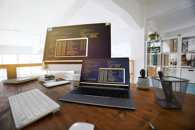 Image d'arrière-plan fisheye de code de programmation noir et orange sur écran d'ordinateur et ordinateur portable dans l'intérieur de bureau contemporain, espace copie
