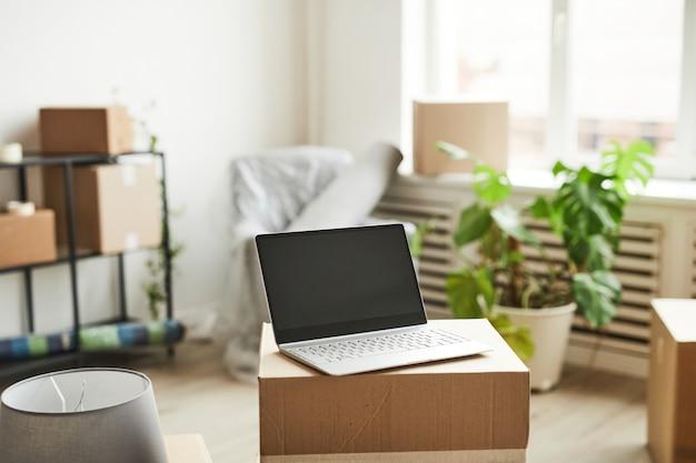Image d'arrière-plan d'un ordinateur portable ouvert avec un écran vide sur des boîtes en carton dans un nouveau déménagement et relogement...