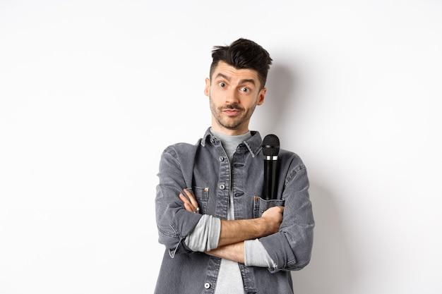 Image d'un artiste masculin drôle ou chanteur, tenant le microphone dans la poche de la veste et regarder la caméra avec les bras croisés, debout sur fond blanc.