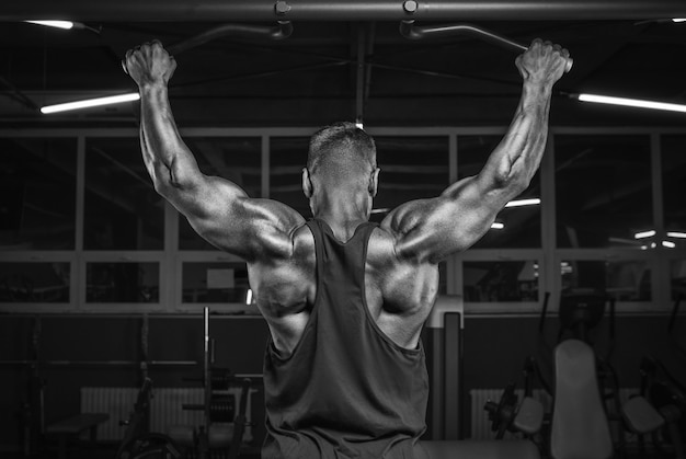 Image d'un athlète puissant faisant une traction dans le gymnase. retour de pompage. concept de remise en forme et de musculation. technique mixte