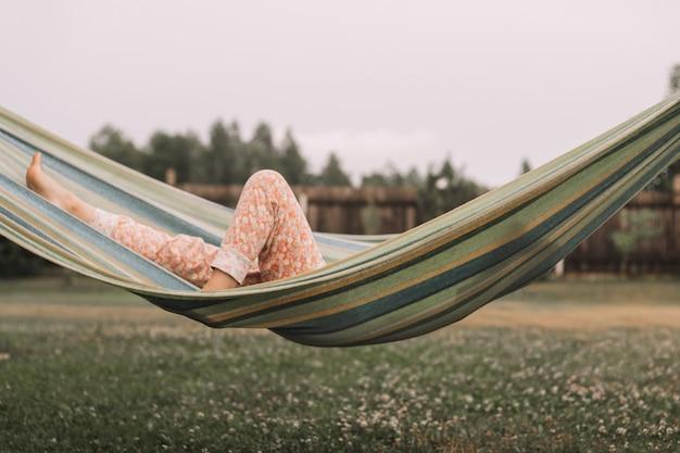 Image authentique de pieds d'enfant allongé sur un hamac. fille se reposant dans la campagne sur fond de clôture en bois et d'herbe verte