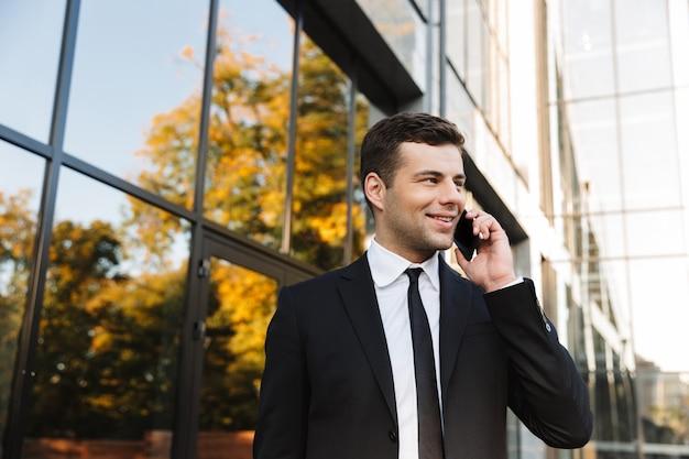 Image d'un beau jeune homme d'affaires heureux marchant à l'extérieur près du centre d'affaires parlant par téléphone mobile.