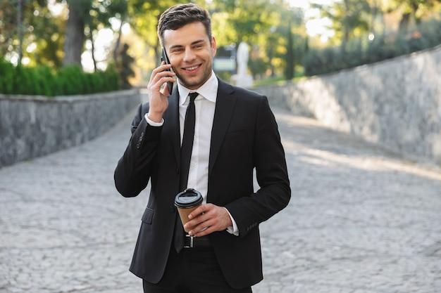 Image d'un beau jeune homme d'affaires heureux marchant à l'extérieur près du centre d'affaires parlant par téléphone portable, boire du café.