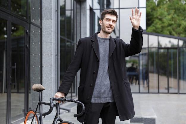 Image de beau jeune homme d'affaires marchant à l'extérieur avec un vélo en agitant.