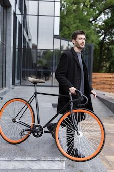 Image de beau jeune homme d'affaires marchant à l'extérieur avec vélo.