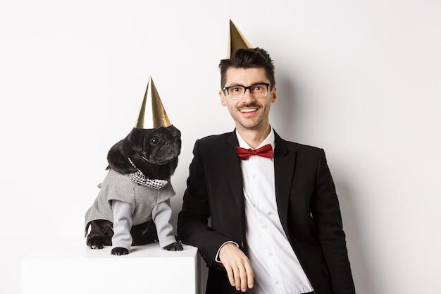 Image d'un beau jeune homme célébrant son anniversaire avec un mignon carlin noir en costume de fête et un cône sur la tête, debout sur fond blanc.