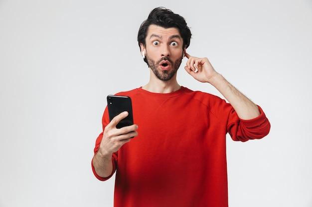 Image d'un beau jeune homme excité posant sur un mur blanc à l'écoute de la musique avec des écouteurs à l'aide de téléphone mobile.