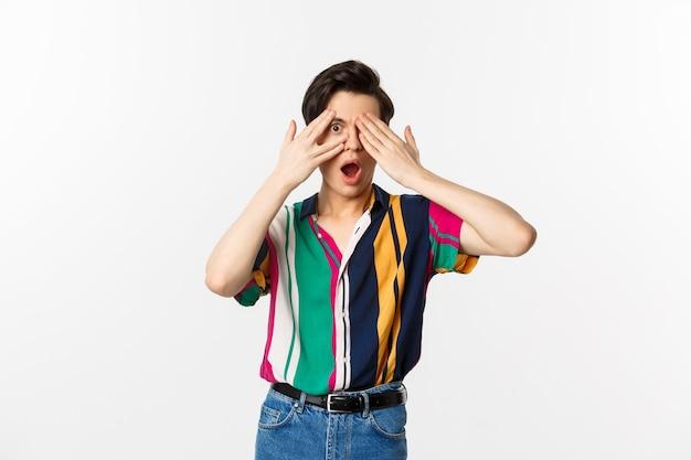 Image de beau jeune homme gay ouvrir les yeux pour voir la surprise, furtivement à travers les doigts avec une émotion étonnée, debout sur fond blanc.