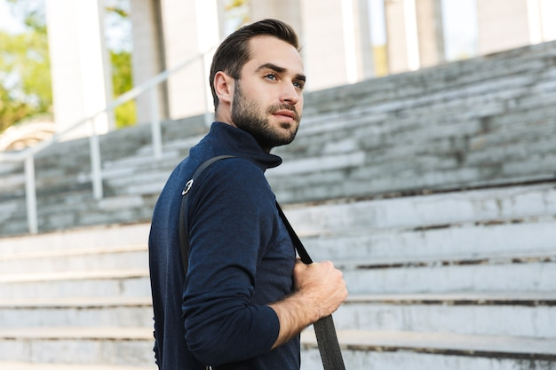 Image d'un beau jeune homme sportif fort et sérieux posant à l'extérieur à l'emplacement du parc naturel tenant le sac.