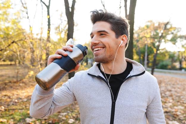 Image d'un beau jeune sportif émotionnel à l'extérieur dans le parc à l'écoute de la musique avec des écouteurs d'eau potable.