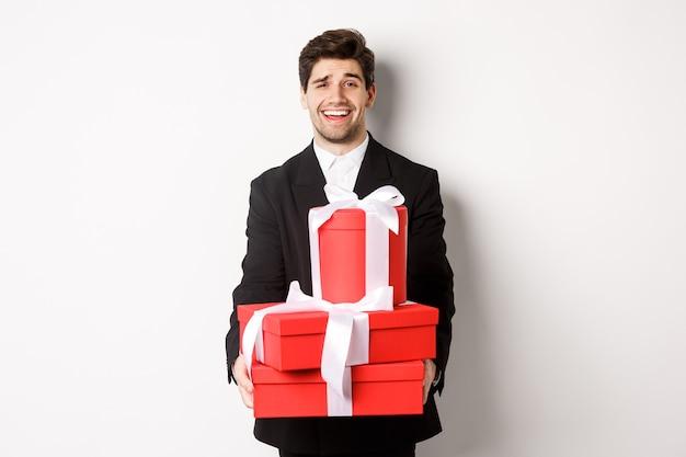 Image de beau mec en costume noir, tenant des cadeaux pour les vacances de noël, debout sur fond blanc