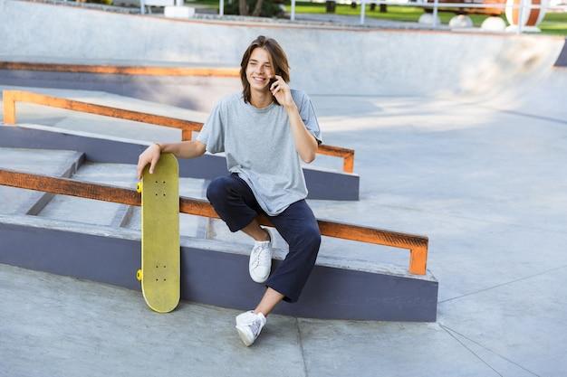 Image de beau mec jeune patineur assis dans le parc avec planche à roulettes parler par téléphone mobile.
