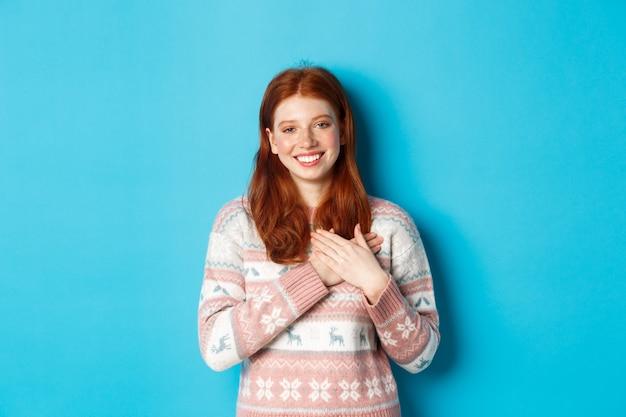 Image d'un beau modèle féminin rousse tenant les mains sur le cœur et souriant, disant merci, reconnaissant, debout sur fond bleu