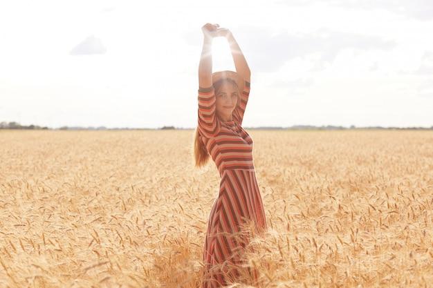Image de beau modèle romantique aux cheveux longs, debout avec les bras levés