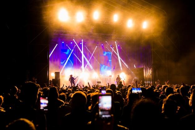 Image de beaucoup de gens appréciant les performances nocturnes