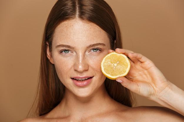Image de beauté d'adorable femme torse nu aux cheveux longs tenant un morceau d'orange, isolé sur fond beige