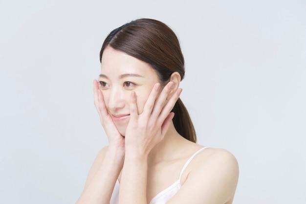 Image de beauté au sol dos blanc / femme asiatique touchant son visage