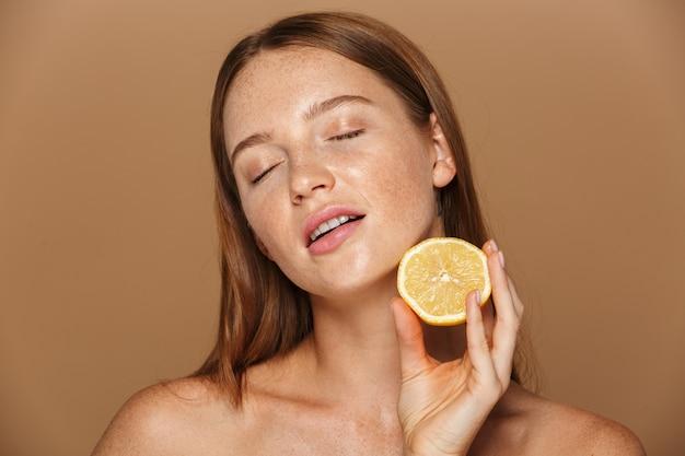 Image de beauté de femme torse nu heureux avec de longs cheveux tenant un morceau d'orange, isolé sur fond beige