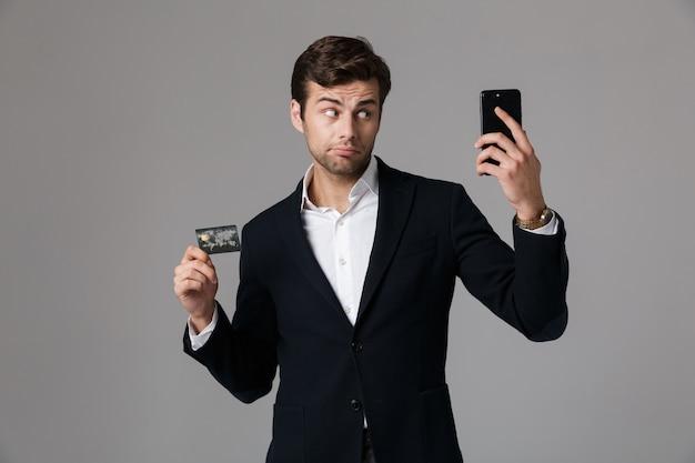 Image de bel homme 30 s en costume d'affaires tenant un téléphone mobile noir et une carte de crédit, isolé sur mur gris