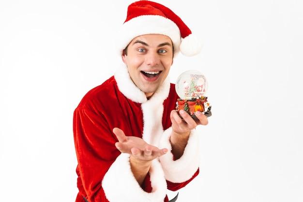 Image de bel homme 30 s en costume de père noël et chapeau rouge tenant boule de noël