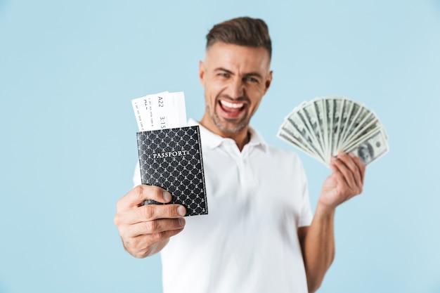 Image d'un bel homme adulte émotionnel excité posant sur un mur bleu tenant un passeport avec des billets et de l'argent.