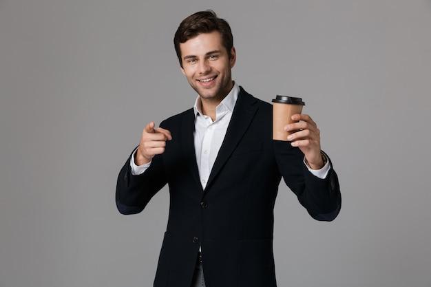 Image de bel homme d'affaires des années 30 en costume souriant et tenant une tasse de papier avec du café, isolé sur mur gris