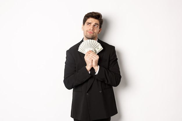 Image d'un bel homme d'affaires en costume noir, détenant de l'argent et pensant à l'investissement, faisant des plans d'achat, debout sur fond blanc.