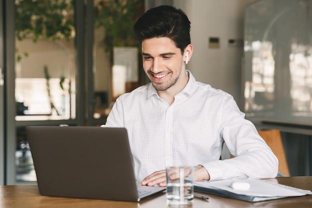 Image de bel homme d'affaires portant une chemise blanche et un oreillette moderne souriant alors qu'il était assis à table au bureau et en regardant un ordinateur portable