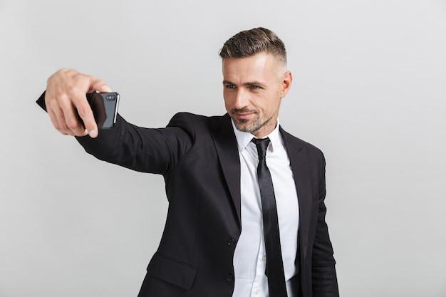 Image d'un bel homme d'affaires réussi en costume formel prenant une photo de selfie sur un téléphone portable isolé