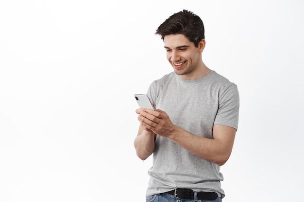Image d'un bel homme écrivant un message, discutant sur les réseaux sociaux et souriant, lisant l'écran d'un téléphone portable, debout sur un mur blanc