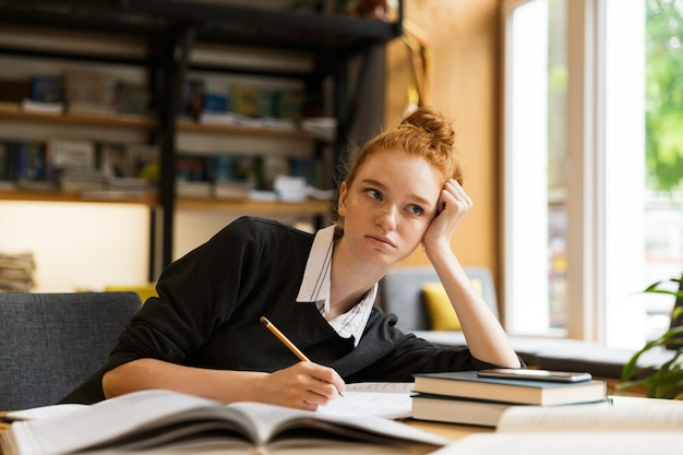 Image de la belle étudiante étudiant, assis au bureau dans la bibliothèque du collège avec mur d'étagère